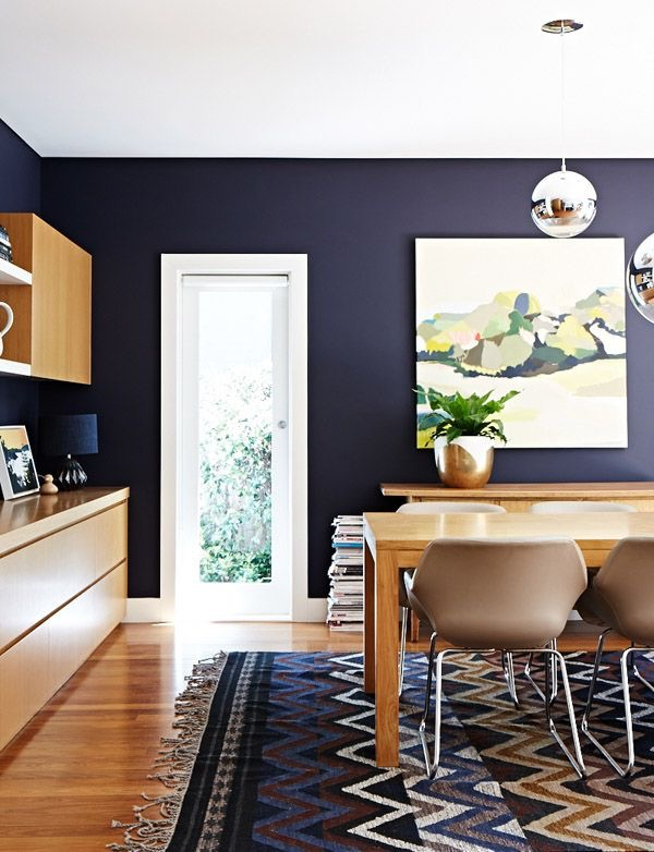 Designer Suzanne's Gorman's dining room contrasts dark walls with timbers and pattern. Artwork by Belynda Henry. Photography Sean Fennessey